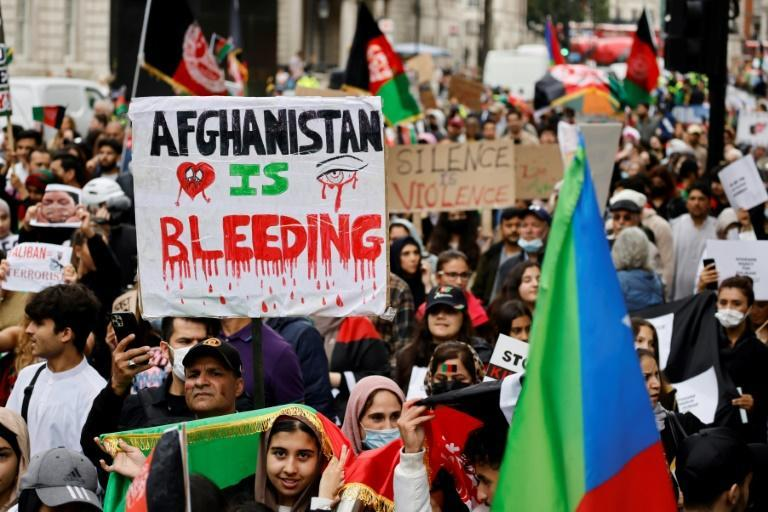 Protesters in London carry placards and wave Afghan flags as they march in solidarity with the people of Afghanistan