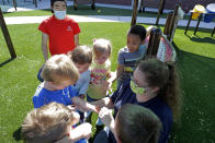 In this May 27, 2020 photo, teachers Jana Blair, right, and Aaron Rainboth, upper left, wear masks as they work with kids examining a spider they found on the playground at the Frederickson KinderCare daycare center, in Tacoma, Wash. In a world weary of the coronavirus, many working parents with young children are now struggling with the decision on when or how they'll be comfortable returning to their child care providers. Frederickson KinderCare has been open throughout the pandemic to care for children of essential workers. (AP Photo/Ted S. Warren)
