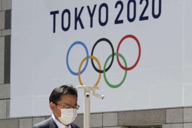 FILE - In this Wednesday, March 25, 2020, file photo, a masked man walks in front of a Tokyo Olympics logo at the Tokyo metropolitan government headquarters building in Tokyo. The Tokyo Olympics have been moved to next year. But countless questions remain. They revolve around 11,000 Olympic athletes and 4,400 Paralympic athletes. They also include 206 national Olympic committees, sports federations, thousands of contracts, and billions of dollars. (AP Photo/Koji Sasahara, File)