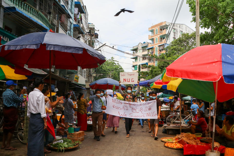 "Anti-coup protesters hold signs that read ""We Support NUG"" that stands for 'national unity government' as they march on a street where vendors sell fresh products Saturday, April 17, 2021 in Yangon, Myanmar. Opponents of Myanmar's ruling junta have declared they have formed an interim national unity government with members of Aung San Suu Kyi's ousted cabinet and major ethnic minority groups.. (AP Photo)"