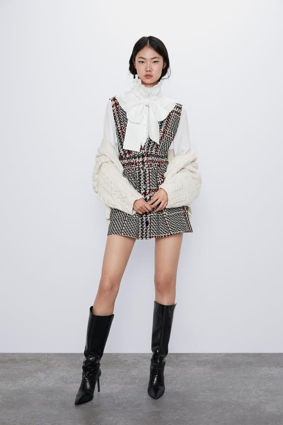 "<p><strong>ZARA</strong></p><p>zara.com</p><p><strong>$49.90</strong></p><p><a href=""https://www.zara.com/us/en/pocket-plaid-pinafore-dress-p08839113.html"" target=""_blank"">Shop Now</a></p><p>Layer a chic bowed blouse and knit cardi over a tweed dress for extra warmth <em>and </em>style.<em></em> Complete the look with knee-high boots to balance out a super-short hemline.</p>"