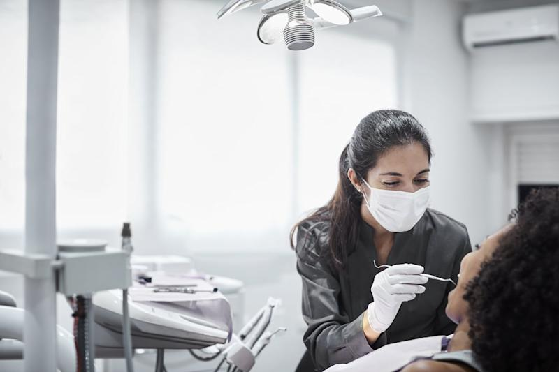 Female dentist examining teeth of patient on chair. Young woman is visiting doctor for dental checkup. They are at clinic.