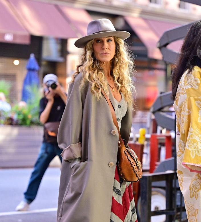 <p>Sarah Jessica Parker wore a gray trench coat matched with a gray zip pin fedora by Larose Paris. </p>