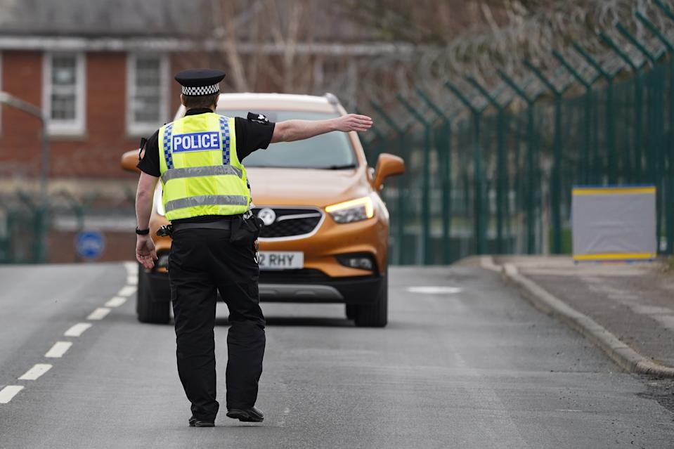 CATTERICK, UNITED KINGDOM - MARCH 28: A Police Officer from North Yorkshire Police speaks to motorists at a vehicle stop to reinforce the importance of social distancing and staying at home to people in Catterick Garrison in a joint operation with military police from 150 Provost Company Royal Military Police as the UK adjusts to life under the Coronavirus pandemic on March 28, 2020 in Catterick, United Kingdom. New police powers to enforce the coronavirus lockdown will allow officers to use force to make people return home if they are in break of emergency laws. Coronavirus (COVID-19) has spread to at least 199 countries, claiming over 27,000 lives and infecting more than 597,000 people. There have now been 14,543 diagnosed cases in the UK and 759 deaths. (Photo by Ian Forsyth/Getty Images)