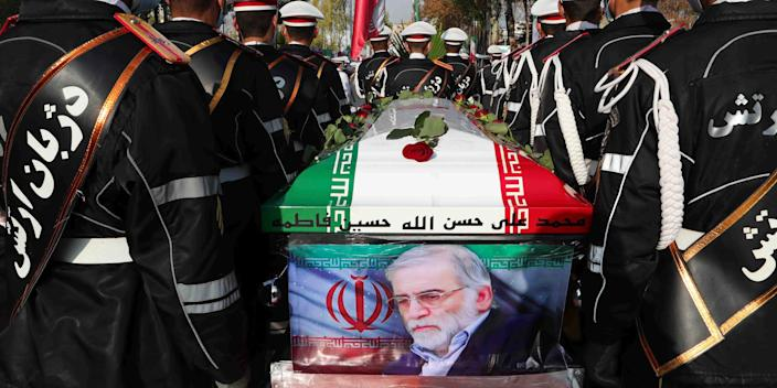 In this photo released by the official website of the Iranian Defense Ministry, military personnel stand near the flag-draped coffin of Mohsen Fakhrizadeh, a scientist who was killed on Friday, during a funeral ceremony in Tehran, Iran, Monday, Nov. 30, 2020.