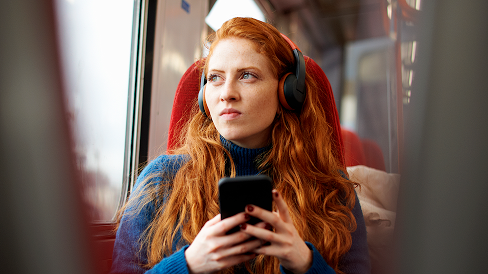Image of young woman listening to podcast on train, looking intense true crime representation