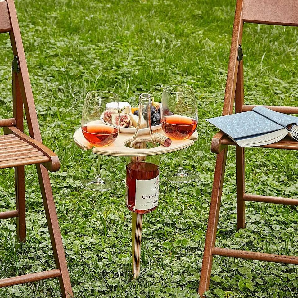"""<h2>Uncommon Goods Outdoor Wine Table</h2> <br>Enhance her outdoor happy hours with this small but mighty wine-table creation — it stakes securely into the ground, boasting space for two glasses plus a bottle and her charcuterie plate. <br><br><em>Shop <strong><a href=""""https://www.uncommongoods.com/fun/wine-dine/wine-gifts"""" rel=""""nofollow noopener"""" target=""""_blank"""" data-ylk=""""slk:Uncommon Goods"""" class=""""link rapid-noclick-resp"""">Uncommon Goods</a></strong></em><br><br><strong>Michael and Ania Shepler</strong> Outdoor Wine Table, $, available at <a href=""""https://go.skimresources.com/?id=30283X879131&url=https%3A%2F%2Fwww.uncommongoods.com%2Fproduct%2Foutdoor-wine-table"""" rel=""""nofollow noopener"""" target=""""_blank"""" data-ylk=""""slk:Uncommon Goods"""" class=""""link rapid-noclick-resp"""">Uncommon Goods</a><br><br><br>"""