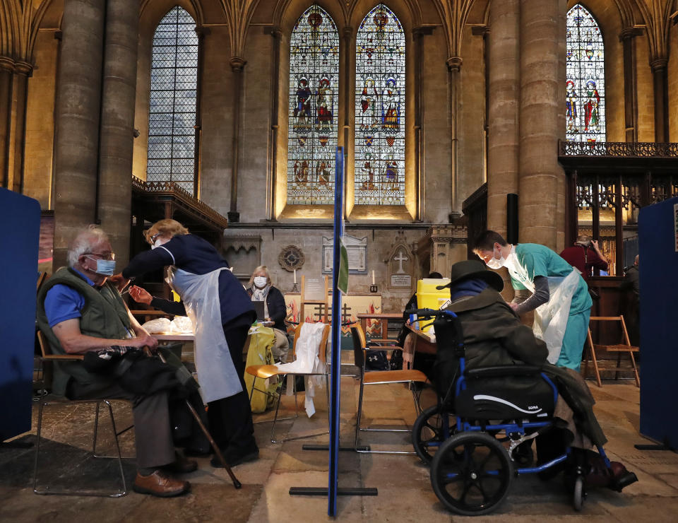 People recieve their Pfizer-BioNTech vaccination inside Salisbury Cathedral in Salisbury, England, Wednesday, Jan. 20, 2021. Salisbury Cathedral opened its doors for the second time as a venue for the Sarum South Primary Care Network COVID-19 Local Vaccination Service. (AP Photo/Frank Augstein)