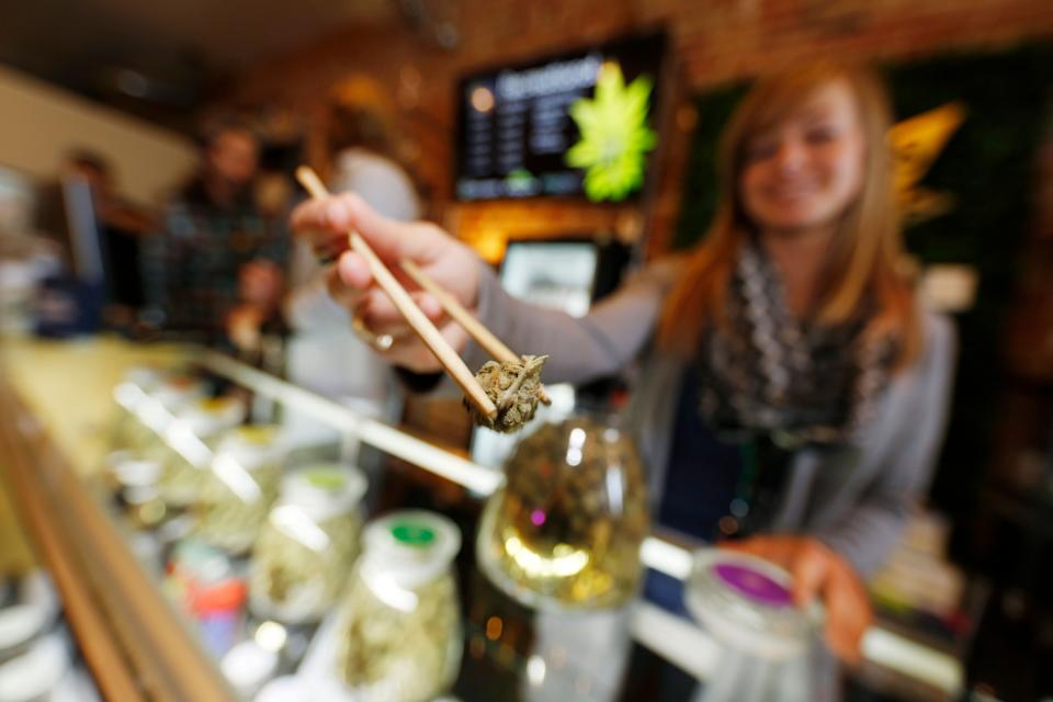 In this Friday, Dec. 18, 2015, photograph, LivWell store manager Carlyssa Scanlon shows off some of the products available in the marijuana line marketed by rapper Snoop Dogg in one of the marijuana chain's outlets south of downtown Denver. LivWell grows the Snoop pot alongside many other strains on its menu. (AP Photo/David Zalubowski)