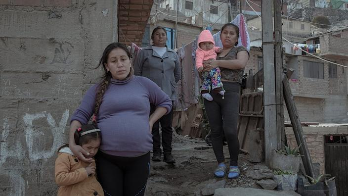 Cinthia Estrada Bolivar (31) and her three-year-old daughter stand in front of their house accompanied by their relatives.