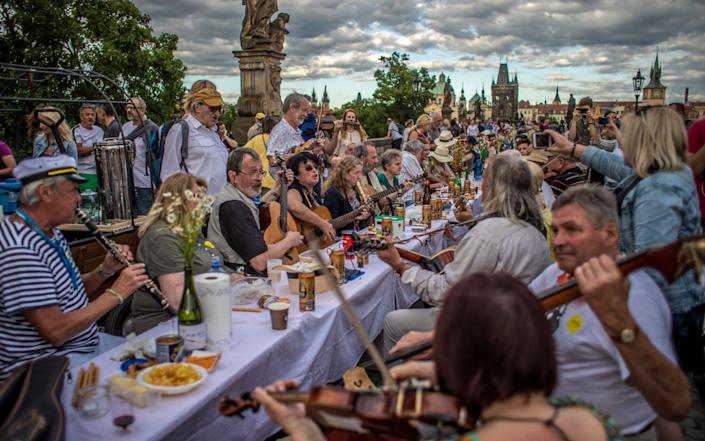 Musicians perform as diners sit at a gigantic table measuring 515 meters (1,690 feet) in length and spanning the entirety of the iconic Charles Bridge in Prague, Czech Republic - MARTIN DIVISEK/EPA-EFE/Shutterstock