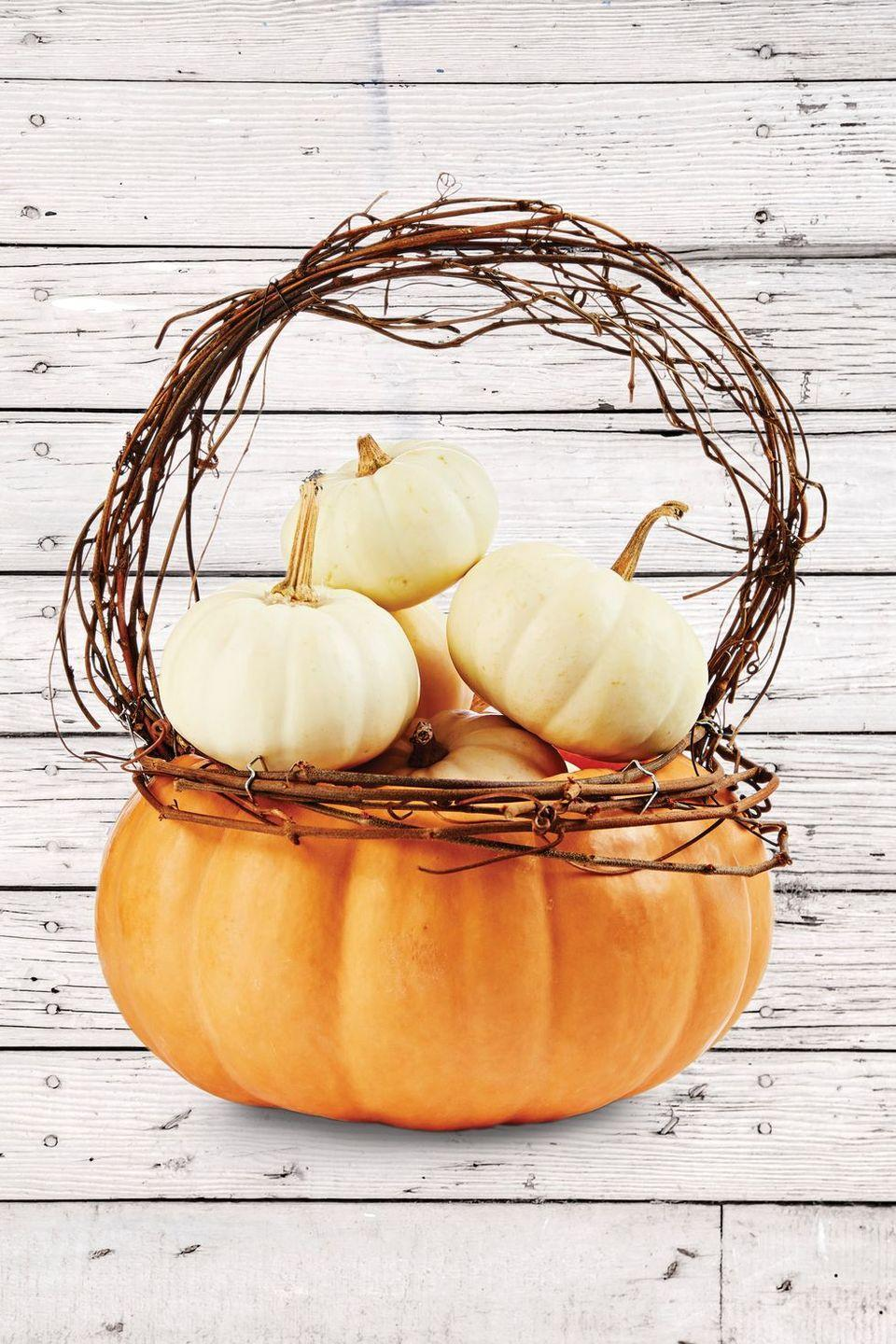 "<p>What's better than a big festive pumpkin for Halloween, you ask? A pumpkin with even more pumpkins inside of it, naturally!<strong><br></strong></p><p><strong>Make the Pumpkin Basket:</strong> Cut off the top quarter of a flat pumpkin (this is a Musquee de Provence variety); scoop out pulp and seeds. Attach lengths of grapevine just below the opening with T-pins. Attach a grapevine handle just inside the opening with T-pins. Nestle mini pumpkins in the basket.</p><p><a class=""link rapid-noclick-resp"" href=""https://www.amazon.com/Ougual-Natural-Grapevine-Garland-Wreaths/dp/B07RD3TBHT/ref=sr_1_1?tag=syn-yahoo-20&ascsubtag=%5Bartid%7C10050.g.279%5Bsrc%7Cyahoo-us"" rel=""nofollow noopener"" target=""_blank"" data-ylk=""slk:Shop Grapevine"">Shop Grapevine</a></p>"