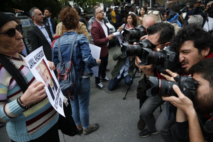 Photographers take pictures of an activist, a member of the Human Rights Association Istanbul branch, holding a poster with a photo of missing Saudi journalist Jamal Khashoggi, during a protest in his support, near the Saudi Arabia consulate in Istanbul, Tuesday, Oct. 9, 2018. Turkey said Tuesday it will search the Saudi Consulate in Istanbul as part of an investigation into the disappearance of a missing Saudi contributor to The Washington Post, a week after he vanished during a visit there. (AP Photo/Lefteris Pitarakis)