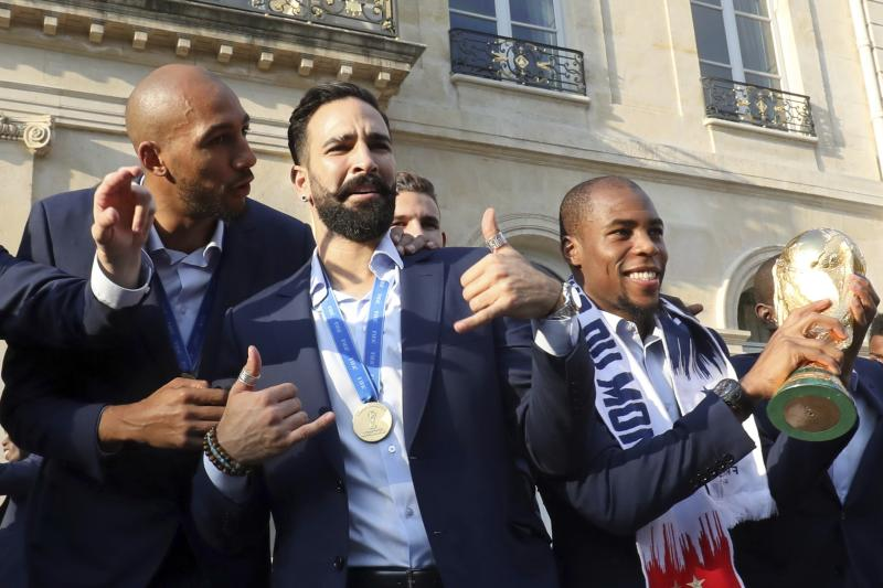 France defender Djibril Sidibe, right, holds the World Cup trophy as midfielder Steven N'Zonzi, left, speaks with defender Adil Rami during an official reception at the Elysee Presidential Palace in Paris, Monday, July 16, 2018. France is readying to welcome home the national soccer team for a parade down the Champs-Elysees, where tens of thousands thronged after the team's 4-2 victory over Croatia Sunday. (Ludovic Marin/Pool Photo via AP)