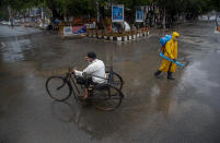 A man rides on a tricycle past a civic worker sanitizing a deserted road during a fresh lockdown imposed in Gauhati, Assam state, India, Sunday, July 12, 2020. India is the world's third worst-affected country by the coronavirus. (AP Photo/Anupam Nath)