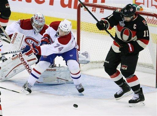 Montreal Canadiens Alexei Emelin (74) attempts to clear the puck as teammate goaltender Carey Price(31) looks on, while Senators Daniel Alfredsson skates by during second period NHL hockey action in Ottawa Dec. 27, 2011. (AP Photo/The Canadian Press, Fred Chartrand)