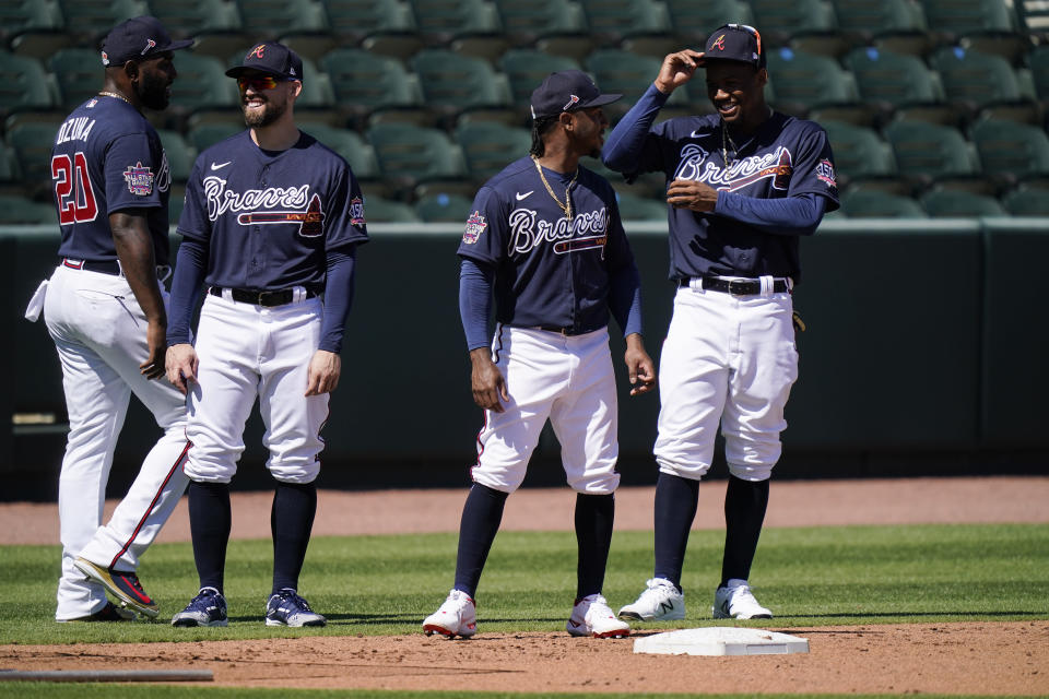 Atlanta Braves' from left, Marcell Ozuna, Ender Inciarte, Ozzie Albies, and Ronald Acuna Jr. wait to run bases during spring training baseball practice on Tuesday, Feb. 23, 2021, in North Port, Fla. (AP Photo/Brynn Anderson)