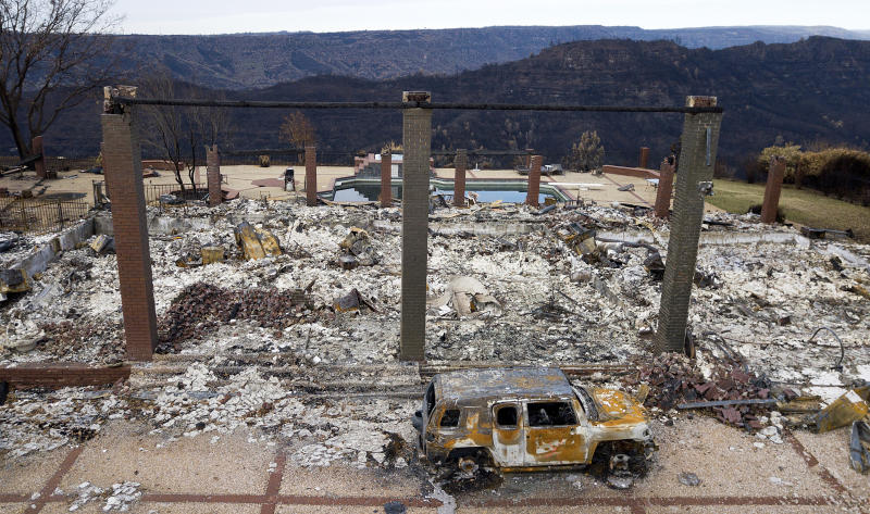 FILE - In this Dec. 3, 2018, file photo, a vehicle rests in front of a home leveled by the Camp Fire in Paradise, Calif. Pacific Gas and Electric has reworked a $13.5 billion settlement with victims of deadly wildfires blamed on the utility to try to prevent it from unraveling after California Gov. Gavin Newsom rejected the company's financial rehabilitation plan. The revision discussed in a bankruptcy court hearing Tuesday, Dec. 17, 2019, removes a provision requiring Newsom to approve the deal as a key piece of PG&E's plan to emerge from bankruptcy protection by June 30. (AP Photo/Noah Berger, File)