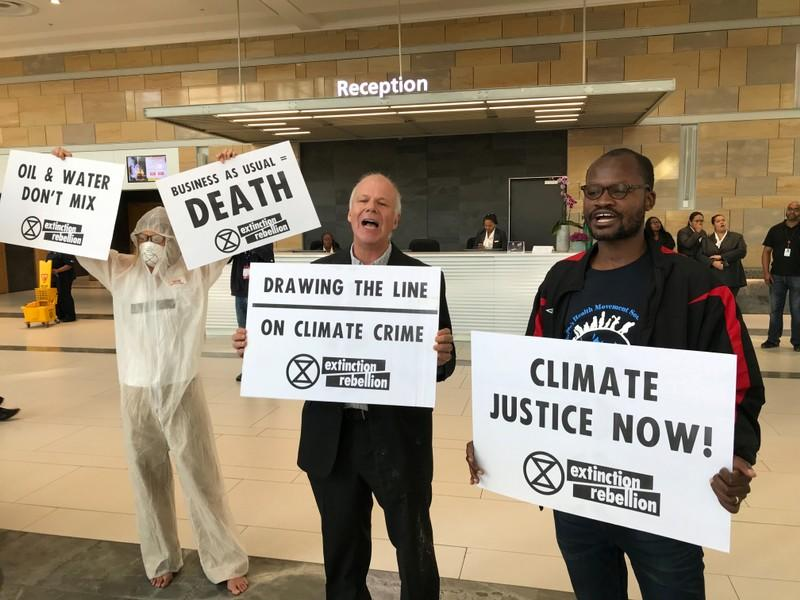 Protestors from climate change awareness collective Extinction Rebellion smear oil across the floor at the lobby of the Africa Oil Week conference in Cape Town