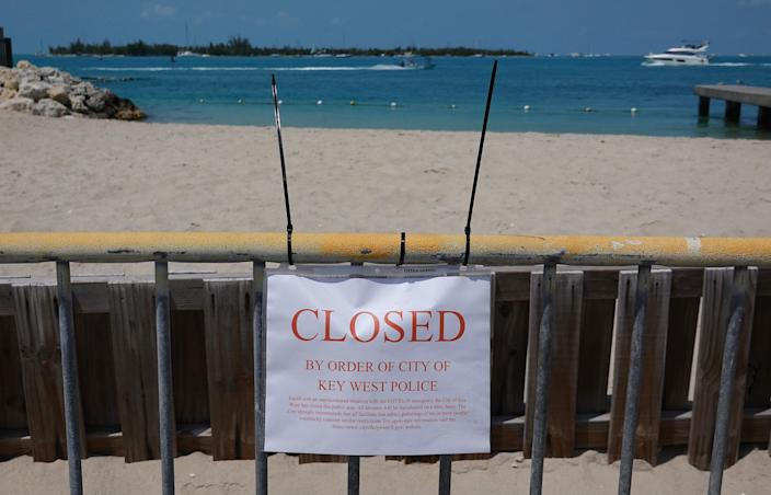 A sign indicates that a beach is closed as the city government takes steps to fight the coronavirus outbreak on March 25, 2020 in Key West, Florida.