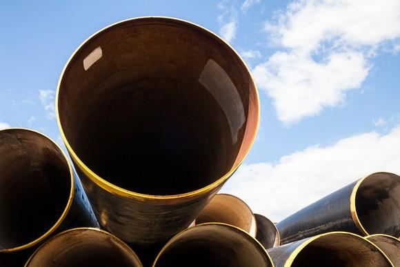 A stack of large pipes with a blue sky in the background.