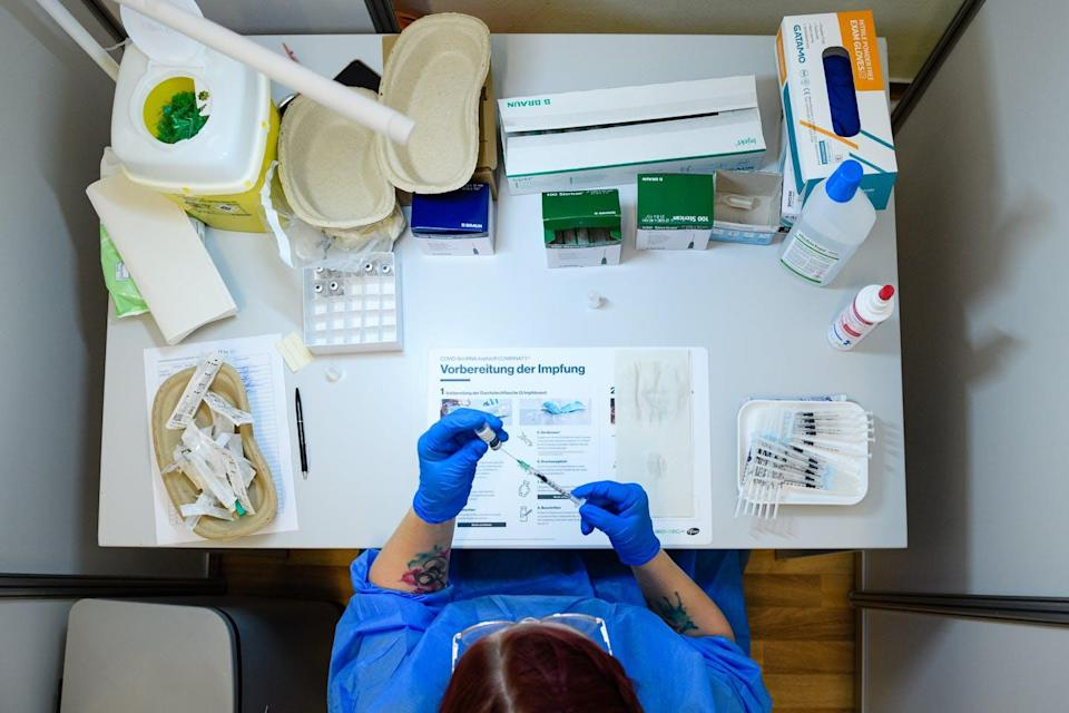 Medical staff prepare a vial of the Pfizer/BioNTech Comirnaty vaccine against COVID-19 in Erfurt, Germany, on Sept. 15.