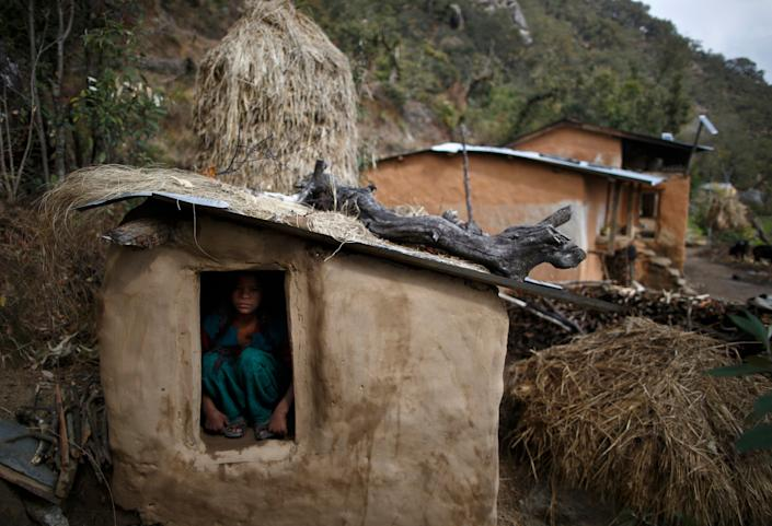 A 14-year-old girl sits inside a chhaupadi shed in the hills of Legudsen village in Achham district in western Nepal in 2014. (Photo: Navesh Chitrakar/Reuters)