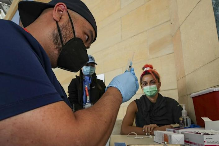 Los Angeles, CA - June 08: William Chang, a RN, prepares a Pfizer vaccine to be administered to Sibelle Yuksek, right, at newly inaugurated site at Union Station on Tuesday, June 8, 2021 in Los Angeles, CA. (Irfan Khan / Los Angeles Times)