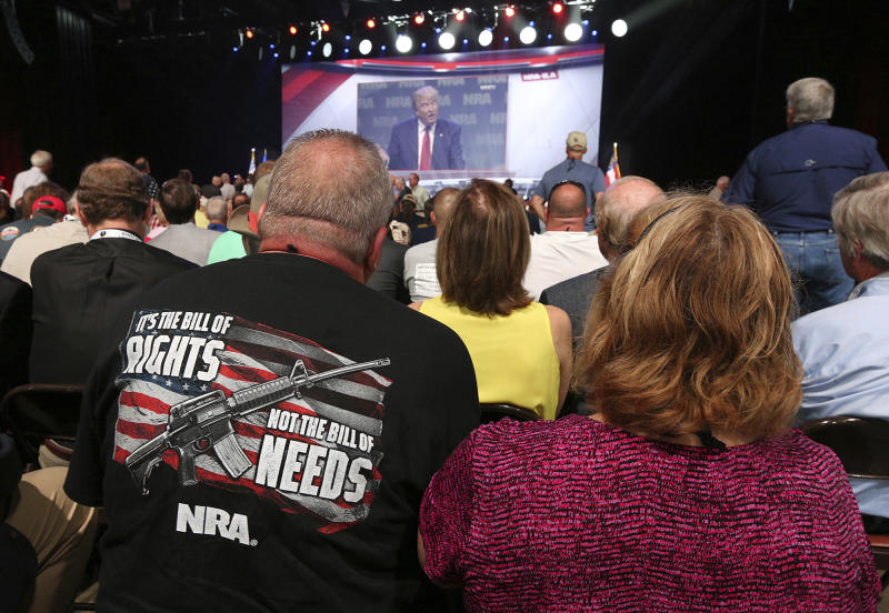 NRA attendees Bill and Karen Geittman watch a video of President Donald Trump while waiting for him to arrive for a keynote at the NRA-ILA Leadership Forum on Friday, April 28, 2017, in Atlanta. (Curtis Compton/Atlanta Journal-Constitution via AP)