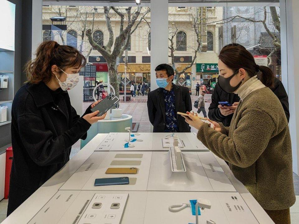 Shoppers check out Oppo's latest flagship Find X3 series 5G smartphones at the company's store in Shanghai on March 12, 2021. Photo: Barcroft Media via Getty Images