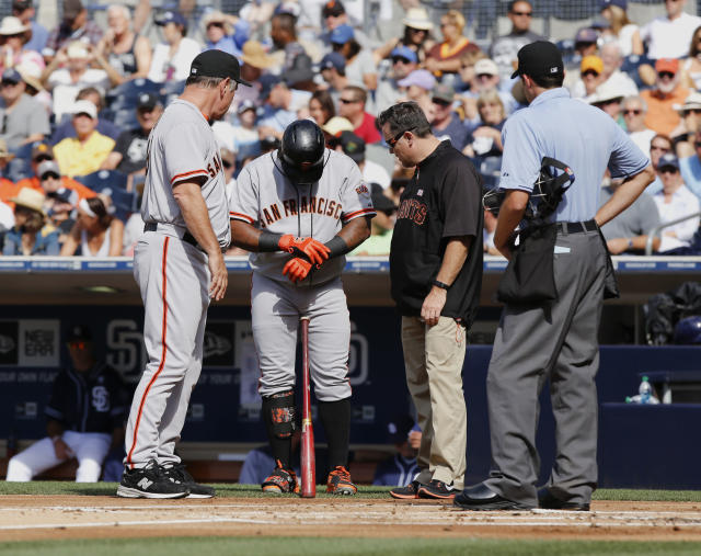 San Francisco Giants manager Bruce Bochy, left, checks on Pablo Sandoval who injured his hand while batting in the first inning against the San Diego Padres of a baseball game Saturday, July 5, 2014, in San Diego. (AP Photo/Don Boomer)