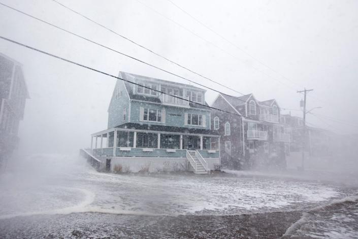 Waves crash over a house in Scituate, Massachusetts, during a storm on March 2, 2018.