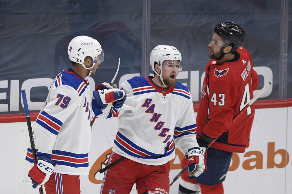 New York Rangers left wing Alexis Lafrenière, center, celebrates his goal with defenseman K'Andre Miller (79) next to Washington Capitals right wing Tom Wilson (43) during the third period of an NHL hockey game, Sunday, March 28, 2021, in Washington. (AP Photo/Nick Wass)