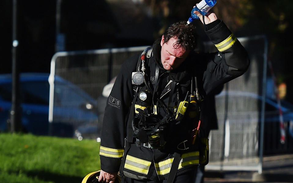 A firefighter pours water over his head after battling a huge fire at the Grenfell Tower - Credit: EPA