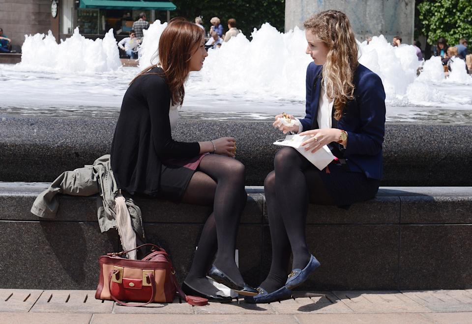 Office workers enjoy the sunshine as temperatures rose to 19c at Canary Wharf in London.