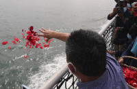 A relative of the victims of Sriwijaya Air flight SJ-182 throw flowers into the Java Sea where the plane crashed on Jan. 9 killing all of its passengers, during a memorial ceremony held on the deck of Indonesian Navy Ship KRI Semarang, near Jakarta in Indonesia, Friday, Jan. 22, 2021. (AP Photo/Tatan Syuflana)