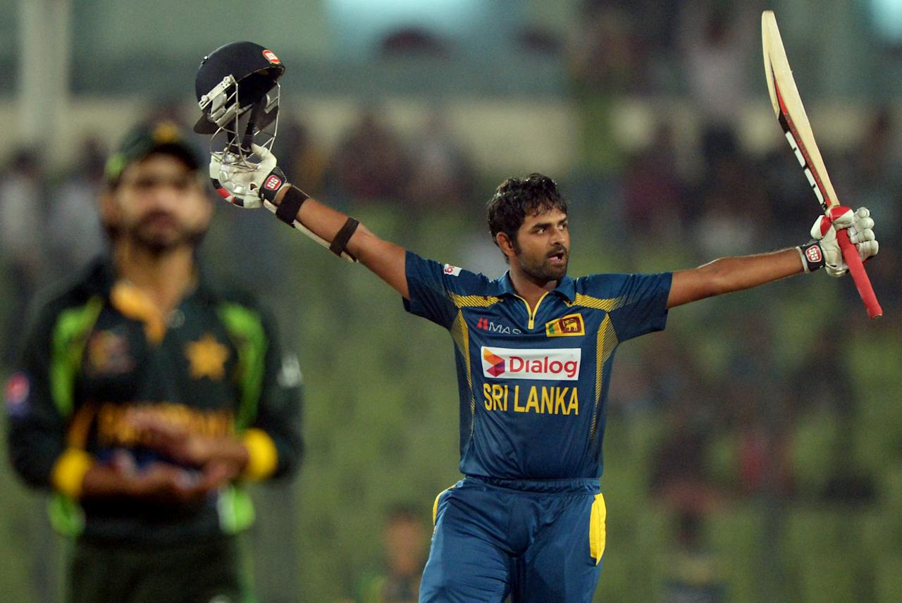 Sri Lankan batsman Lahiru Thirimanne celebrates after scoring a century (100 runs) as Pakistani fielder Fawad Alam (L, background) claps during the final match of the Asia Cup one-day cricket tournament between Pakistan and Sri Lanka at the Sher-e-Bangla National Cricket Stadium in Dhaka on March 8, 2014. AFP PHOTO/Dibyangshu SARKAR