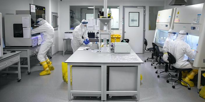 """Scientists work with samples taken for testing for the coronavirus on May 12, 2020. <p class=""""copyright"""">REUTERS/Marko Djurica</p>"""