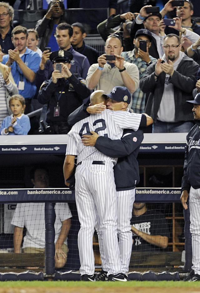 CORRECTS WINNING TEAM TO RAYS - New York Yankees manager Joe Girardi hugs pitcher Mariano Rivera (42) during the ninth inning of a baseball game against the Tampa Bay Rays on Thursday, Sept. 26, 2013, at Yankee Stadium in New York. Rivera was playing in his final home game before retiring. The Rays won 4-0. (AP Photo/Bill Kostroun)