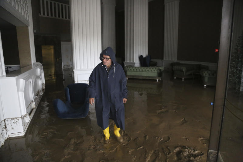 A man walks inside the reception of a flooded hotel after heavy rain fell overnight near Kerynia city in the Turkish Cypriots breakaway north part of Cyprus, Thursday, Dec. 6, 2018. Police in the breakaway north of ethnically split Cyprus say the bodies of three people have been recovered from river beds at two different locations after flash floods are believed to have swept them away. (AP Photo/Petros Karadjias)
