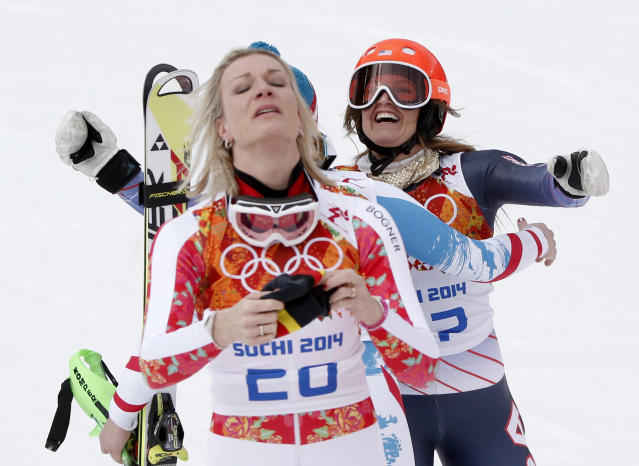 Germany's Maria Hoefl-Riesch, foreground, and United States' Julia Mancuso react to their gold and bronze medal finishes in the women's supercombined at the Sochi 2014 Winter Olympics, Monday, Feb. 10, 2014, in Krasnaya Polyana, Russia. (AP Photo/Christophe Ena)