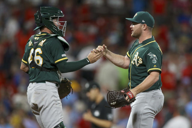 Oakland Athletics catcher Beau Taylor (46) and relief pitcher Liam Hendriks congratulate each other after the team's 2-0 win over the St. Louis Cardinals in a baseball game Wednesday, June 26, 2019, in St. Louis. (AP Photo/Scott Kane)