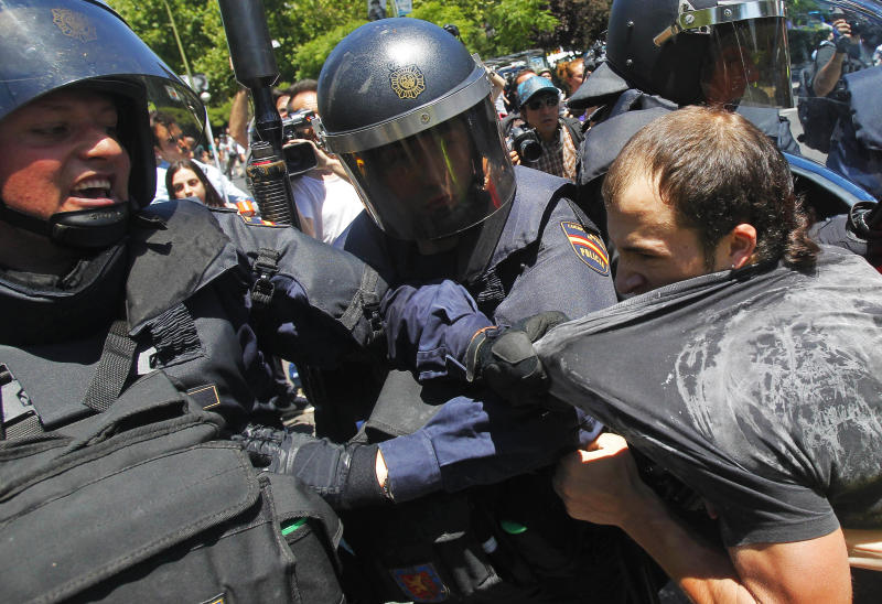 A demonstrator is detained by the riot police during a coal miners march to the Minister of Industry building in Madrid, Wednesday, July 11, 2012. Coal miners angered by huge cuts in subsidies converged on Madrid Tuesday for protest rallies after walking nearly three weeks under a blazing sun from the pits where they eke out a living. (AP Photo/Andres Kudacki)