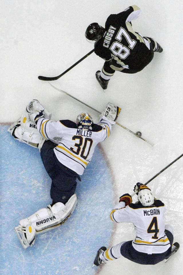 Buffalo Sabres goalie Ryan Miller (30) makes the save on a shot by Pittsburgh Penguins' Sidney Crosby (87) in the second period of an NHL hockey game in Pittsburgh, Monday, Jan. 27, 2014. The Penguins won 3-0. (AP Photo/Gene J. Puskar)