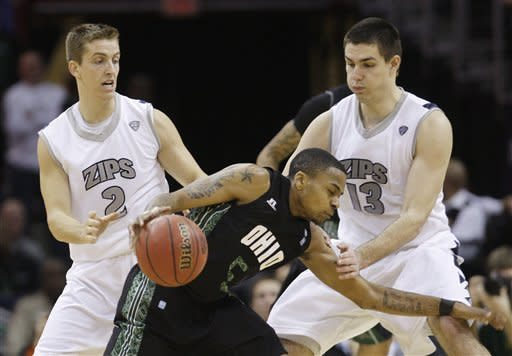 Ohio's D.J. Cooper (5) drives past Akron's Brian Walsh (2) and Nikola Cvetinovic (13) in the second half during an NCAA college basketball championship game in the Mid-American Conference men's tournament on Saturday, March 10, 2012, in Cleveland. Ohio won 64-63. (AP Photo/Tony Dejak)