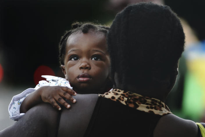 A Haitian migrant carrying a baby walks along the highway in Huixtla, Chiapas state, Mexico, early Thursday, Sept. 2, 2021, in their journey north toward the U.S. (AP Photo/Marco Ugarte)