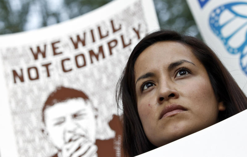 """Diana Perez listens to speakers as she joins dozens who rally in front of  U.S. Immigration and Customs Enforcement building, a day after a portion of Arizona's immigration law took effect, Wednesday, Sept. 19, 2012, in Phoenix. Civil rights activists contend will lead to systematic racial profiling, as the protesters chanted """"No papers, no fear.""""(AP Photo/Ross D. Franklin)"""