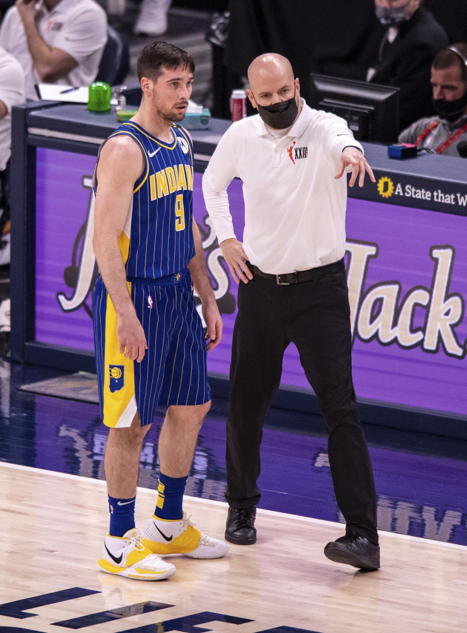 Indiana Pacers head coach Nate Bjorkgren, right, talks with guard T.J. McConnell (9) during a break in the first half of an NBA basketball game against the Los Angeles Lakers in Indianapolis, Saturday, May 15, 2021. (AP Photo/Doug McSchooler)