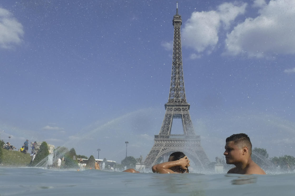 People cool off in the fountain of the Trocadero in Paris (AP Photo/Alessandra Tarantino)