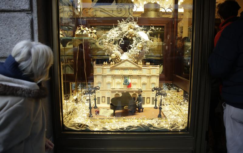 """A woman looks at a cake in the shape of La Scala opera house displayed in the window of Cava bakery, in downtown Milan, Italy, Saturday, Dec. 7, 2019. Milan's storied La Scala opera house opens its 2019-2020 season on Saturday with Puccini's """"Tosca,"""" which stars Russian soprano Anna Netrebko as the object of unwanted sexual attention from a powerful authority figure. (AP Photo/Luca Bruno)"""